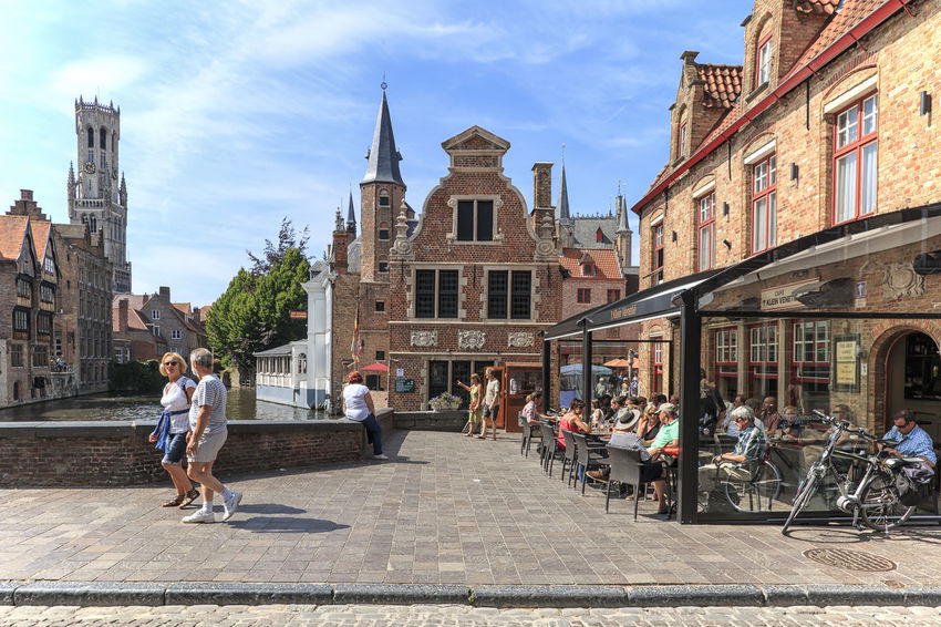 Bruges, Belgium - July 7, 2017: Tourists eating mussels and french fries in the restaurants not far from the Market Square of Bruges Beer Belgium Brugge Chocolate Dijver Canal Duvel Flanders Panoramic View Provinciaal Hof West Flanders Aerial View Belfry Tower Bikes Bruges Europe Flower French Fries Holland Market Square Medieval Town Mussels