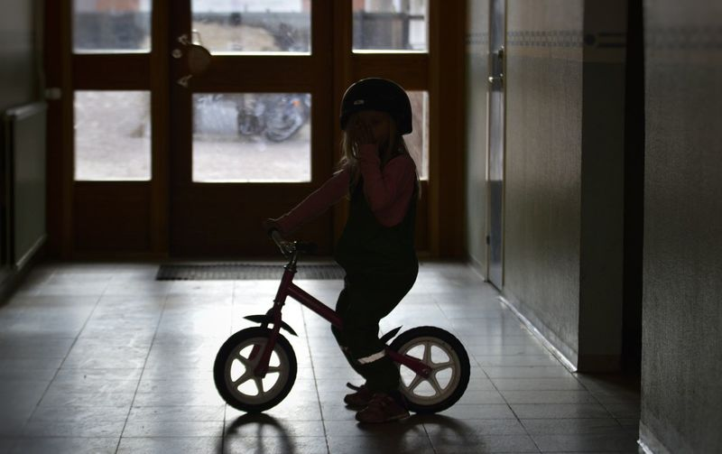 Full length girl with bicycle in corridor