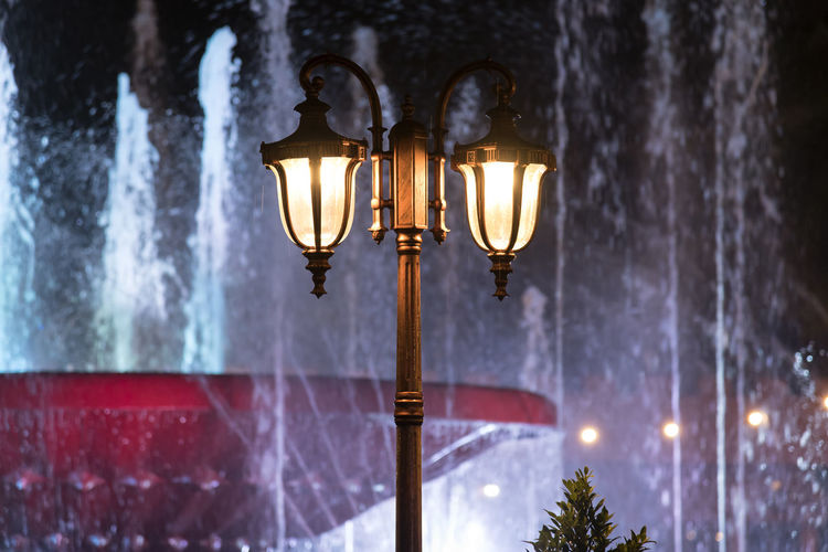 Low angle view of illuminated street lights against fountains in city at night
