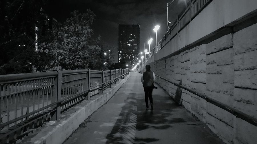 Rear view of woman walking on road at night