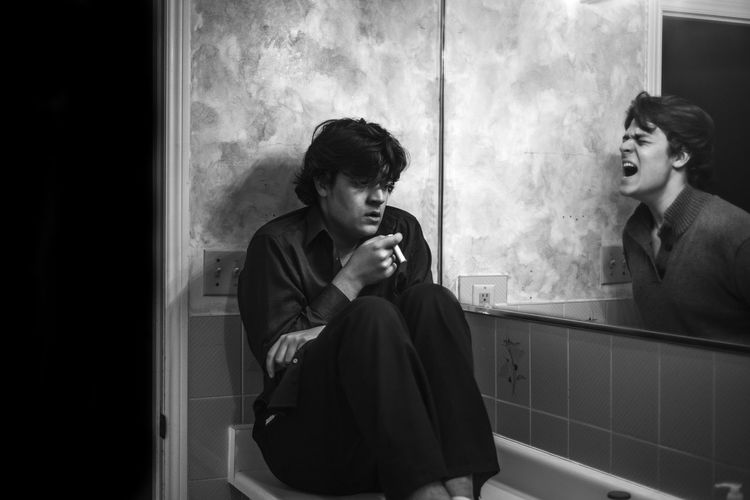 Multiple image of man smoking cigarette while shouting in bathroom in front of mirror