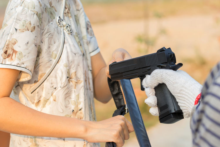 Adult Aggression  Care Casual Clothing Clothing Day Focus On Foreground Gun Hand Holding Leisure Activity Lifestyles Men Midsection Nature Outdoors People Real People Side View Two People Weapon Women