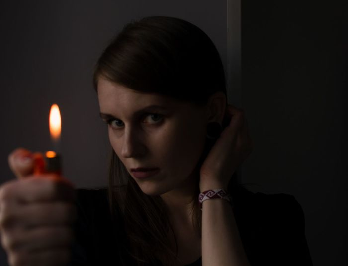 Close-up portrait of young woman holding lighter