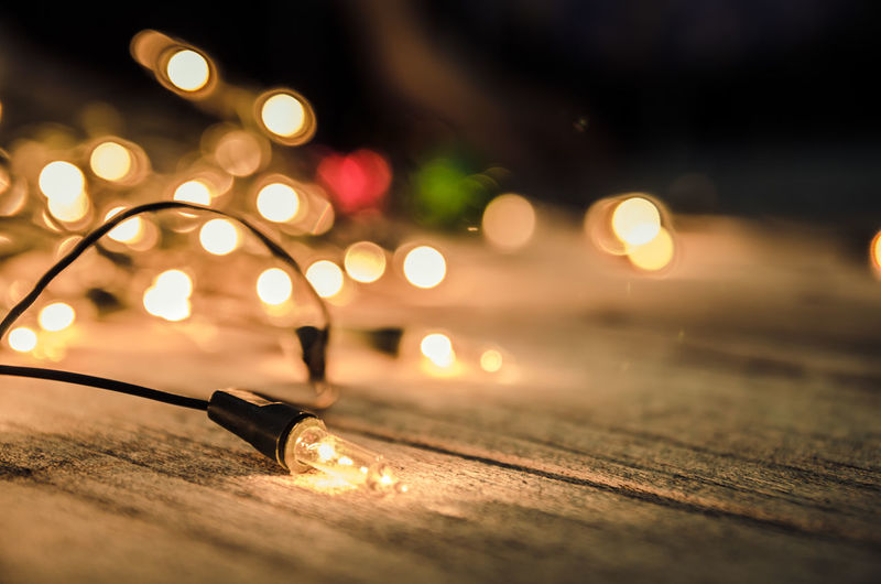 Close-Up Of Illuminated String Lights On Table During Christmas