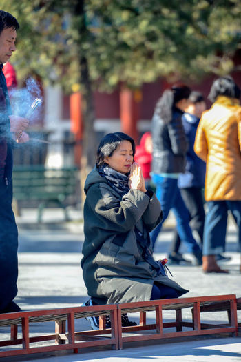 Worshippers hold incense sticks and pray at Yonghegong Lama Temple in Beijing, China. ASIA Beijing Lama Temple Monastery Smoke Worshippers Budhism Casual Clothing Child Childhood China Clothing Day Focus On Foreground Group Of People History Incidental People Lama Leisure Activity Lifestyles Looking Males  Men Outdoors People Prayer Real People Religion Seat Sitting Stick Temple Warm Clothing Winter Women Yonghe Yonghegong