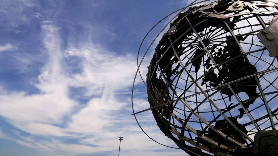 Low angle view of metal globe against sky