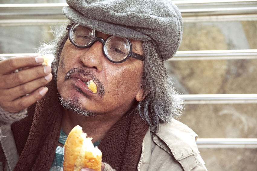 Homeless man on street and eating old bread. Beard Close-up Clothing Eating Eyeglasses  Facial Hair Food Food And Drink Freshness Front View Glasses Headshot Holding Indulgence Leisure Activity Lifestyles One Person Portrait Real People