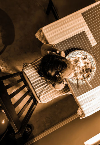 Directly above shot of girl eating food sitting by table