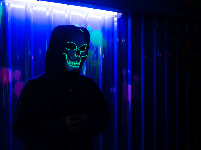 Serial killer wearing neon skull mask at halloween costume party with colorful background.