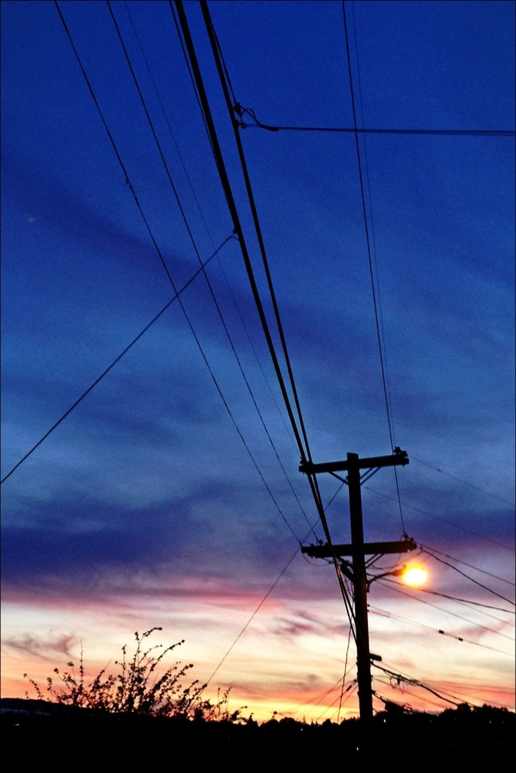power line, electricity pylon, silhouette, sunset, power supply, electricity, sky, connection, cable, fuel and power generation, low angle view, technology, cloud - sky, scenics, tranquility, beauty in nature, tranquil scene, power cable, blue, dusk