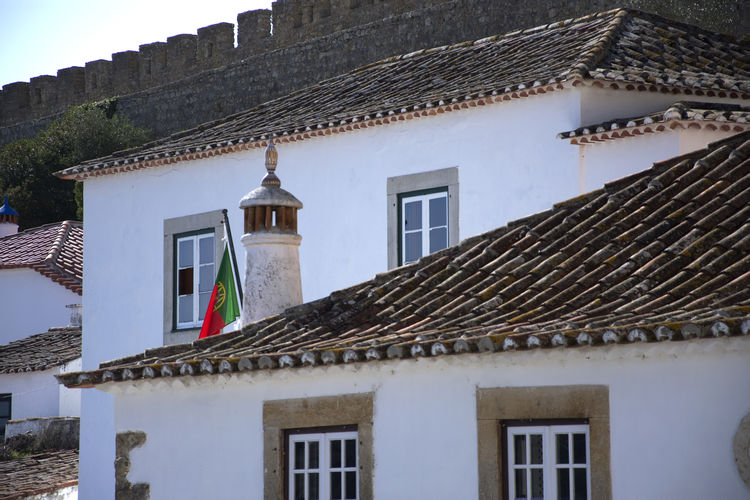 Impressions of the medieval city of Óbidos in Portugal. MedievalTown Obidos Portugal Portugal Architecture Building Exterior Built Structure Day Flag House Medieval Castle No People Outdoors Residential Building Roof Roof Tile Tiled Roof  Tourism Town Óbidos