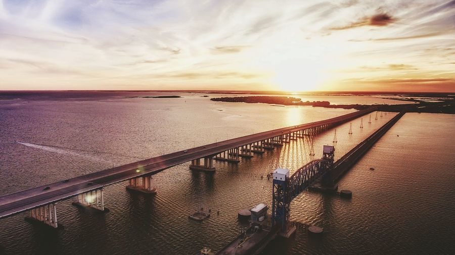 View of bridge over calm sea at sunset