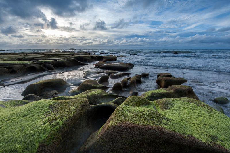 seascape with rocks formation covered by green moss. Beach Beauty In Nature Cloud - Sky Day Horizon Horizon Over Water Land Moss Nature No People Rock Rock - Object Scenics - Nature Sea Sky Solid Tranquil Scene Tranquility Water
