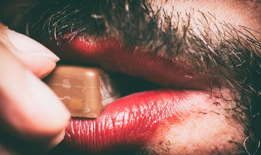 Extreme close up of a man eating chocolate