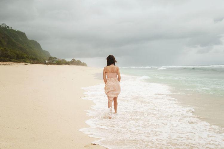 Rear view of woman walking at shore