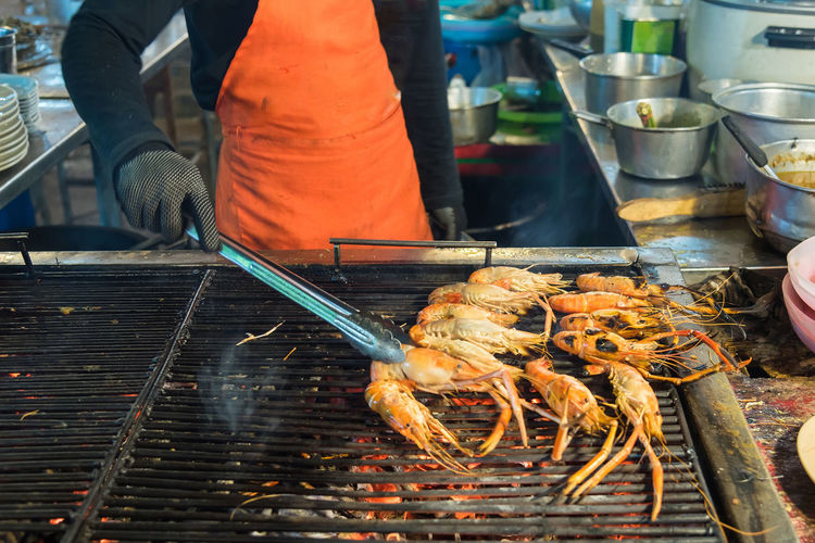 Midsection Of Man Preparing Shrimps On Barbecue