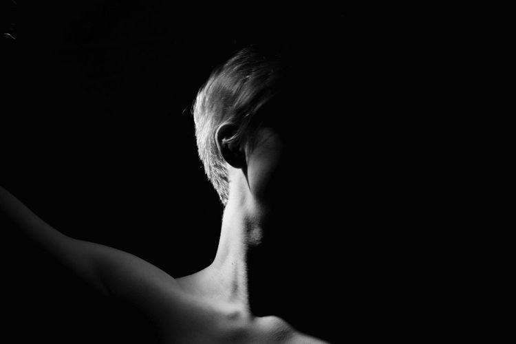 Shirtless man in darkroom