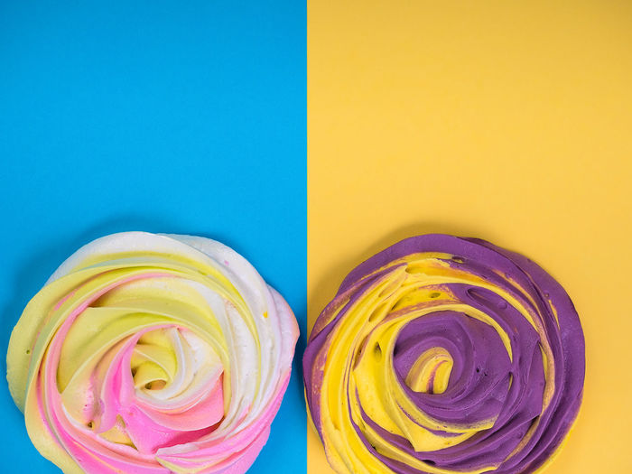 Multi Colored Yellow Blue Indoors  Colored Background Close-up No People Studio Shot Copy Space Food Food And Drink Freshness Pink Color Flower Two Objects Sweet Food Vibrant Color Sweet Still Life Swirl Turquoise Colored Blue Background Temptation