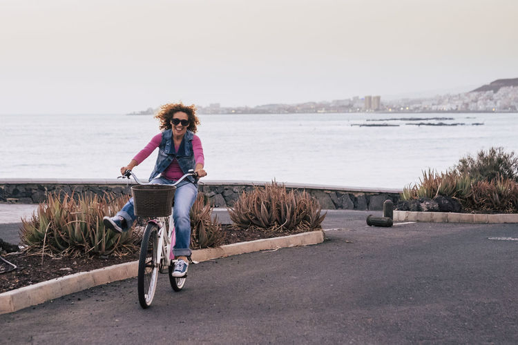 Portrait Of Mature Woman Riding Bicycle On Road Against Clear Sky