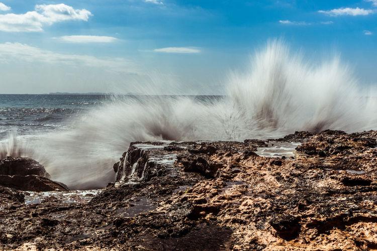 Sea waves splashing on rocky shore against sky