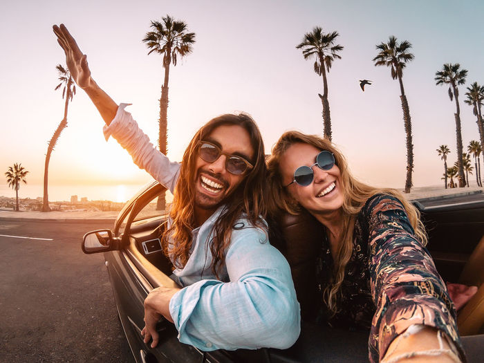 Portrait of cheerful couple wearing sunglasses in convertible against sky