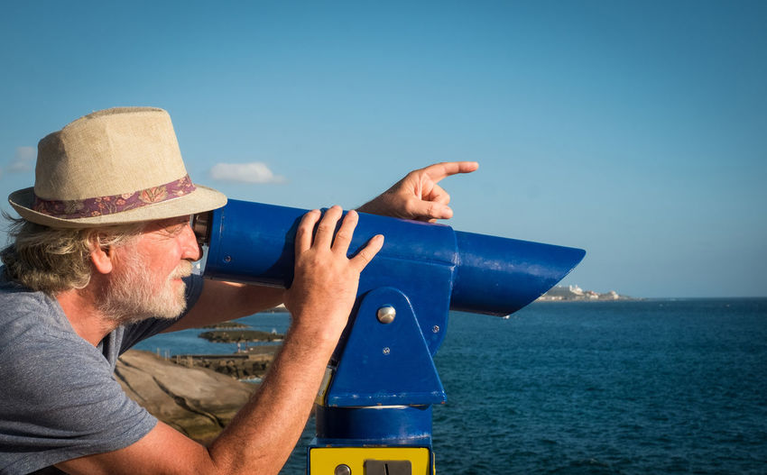 Man wearing hat looking through coin-operated telescope by sea against blue sky