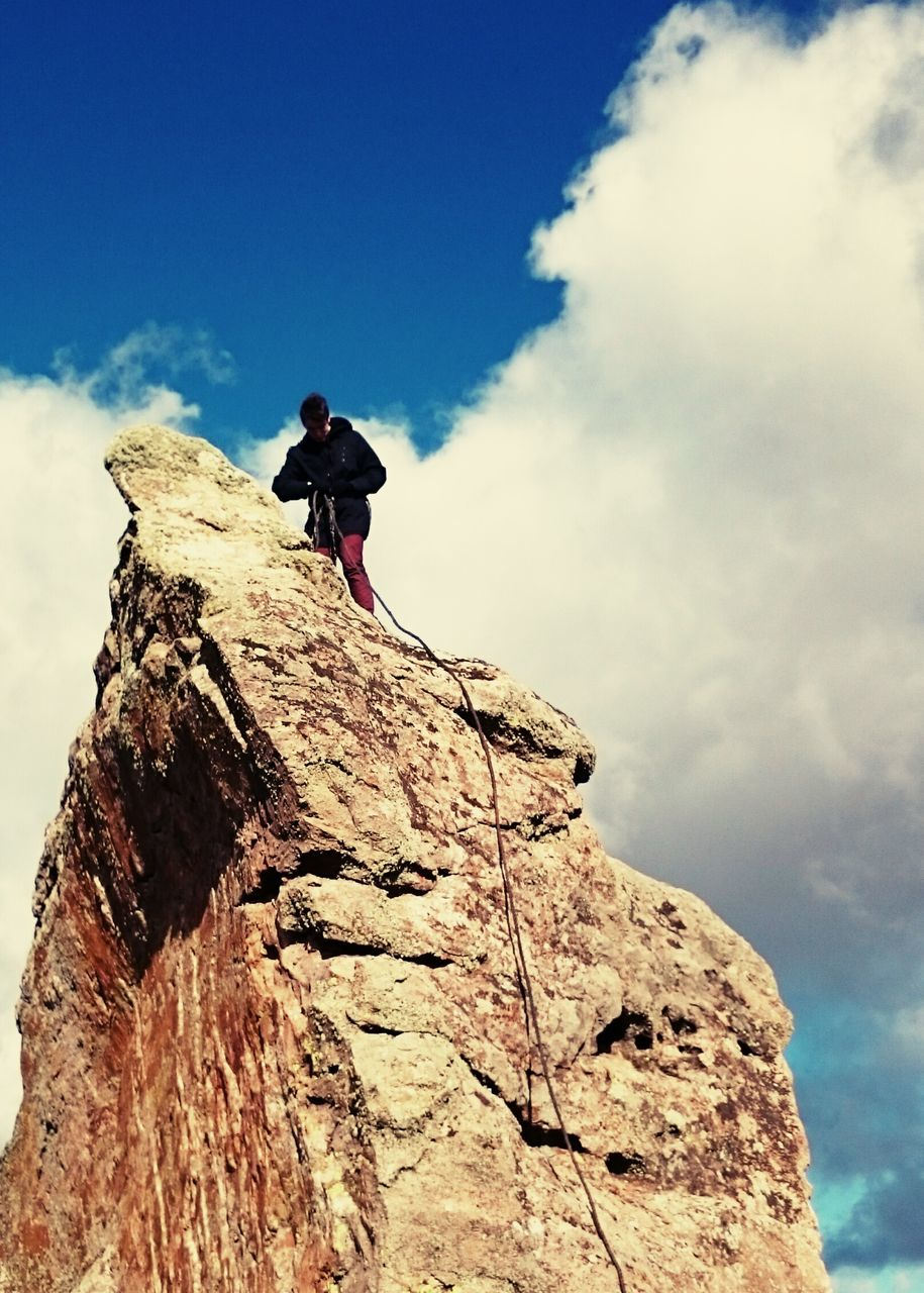 rock - object, adventure, sky, low angle view, cloud - sky, day, nature, full length, climbing, outdoors, leisure activity, extreme sports, one person, risk, real people, beauty in nature, rock climbing, cliff, scenics, exploration, courage, lifestyles, challenge, tranquility, mountain, young adult, people