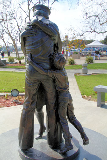Homecoming. By Artist: Stanley Bleifeld, Location: Harbor Drive at G Street Mole, San Diego, California. This seven-foot bronze sculpture depicts the joyous reunion of a sailor, his wife and child upon his return from a sea deployment with the Navy. It's a scene repeated countless times over the years along the San Diego waterfront and in other homeports of the Navy. Stanley Bleifeld's Homecoming perfectly captures the magical and happy moment of reunion and is a fitting tribute to the vital role played by these non-uniformed members of the Navy team. The reunion portrayed here evokes liberation from awesome loneliness and fear, for all the participants. For all of the adventure involved, going to sea is still plain hard work and filled with uncertainties for those who go and those who stay behind. Whole lives have changed during this separation, and great spans of time lost can never be recovered. The Homecoming is as much a celebration of success as it is liberation from hardship. It eloquently attests to a shared sense of accomplishment, recognition by sailor, wife and child that each has done the duty set before them. Not only is theirs the triumph of survival, it is a triumph of achievement. True, there is a romance in going to sea, but the Homecoming reminds us that some of what the Sailors brag about is really the romance of coming back home. San Diego, California, Navy, Statue, Homecoming, Pier, Bay, Harbor, Sailor, Wife, Child,