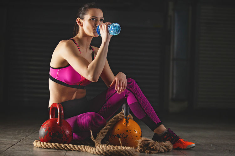 Full Length Of Woman Drinking Water After Workout While Sitting In Gym