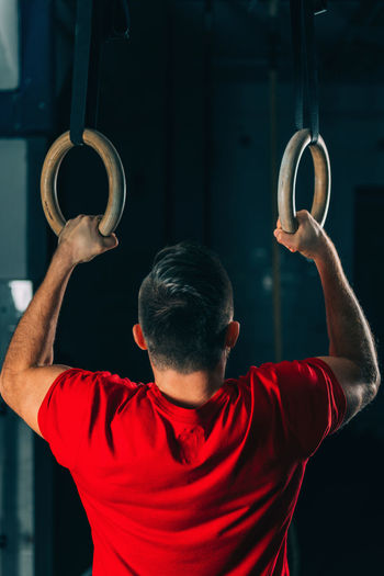 Rear View Of Male Athlete Exercising On Gymnastics Rings In Gym