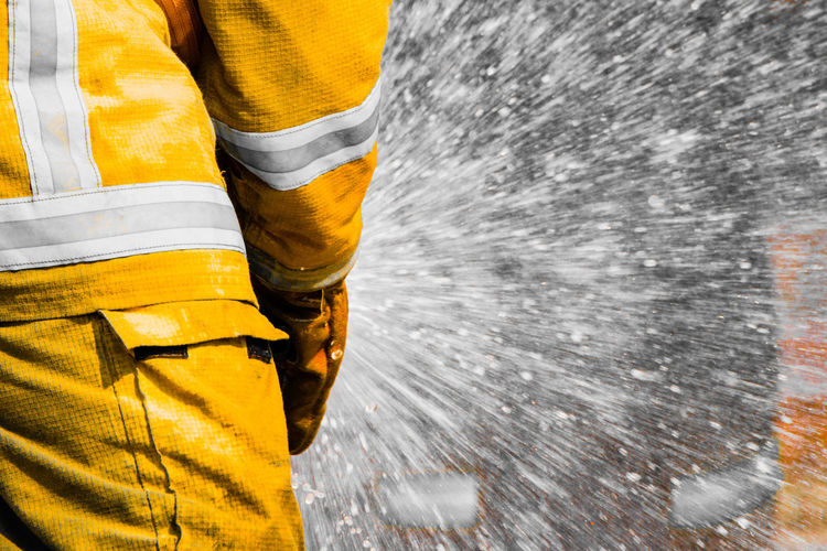 Midsection of firefighters spraying water