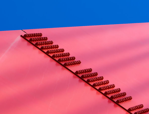 A bridge support, painted bold red, sports dozens of nuts and bolts, standing out against the blue sky. Abstract Blue Blue Sky Bold Colors Bridge Close-up Graphic Design Heavy Metal Industrial Iron Metal Minimalism Polarized Red Simplicity Sky