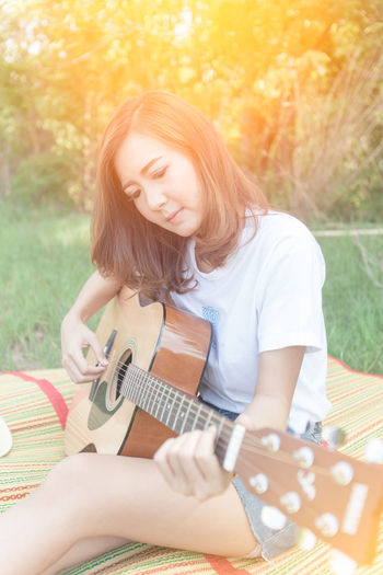 Young woman playing guitar on grassy field at park