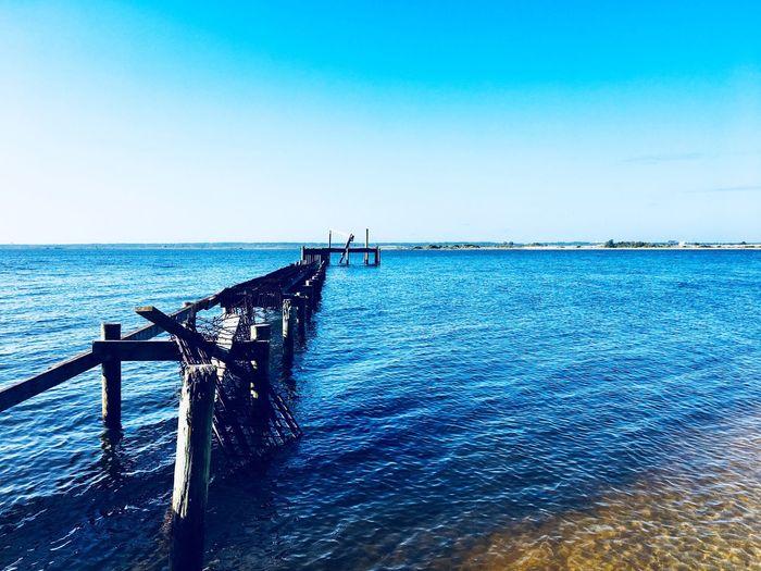 Pier over sea against clear blue sky