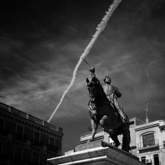 Low Angle View Of Statute By Building Against Cloudy Sky