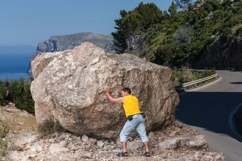 Road impassable by a landslide, on the coastal road from Andratx to Soller on Mallorca, Spain in Europe. Adventure Arms Raised Casual Clothing Day Formation Full Length Human Arm Leisure Activity Lifestyles Men Mountain Nature One Person Outdoors Plant Real People Rear View Rock Rock - Object Rock Formation Solid Standing Tree