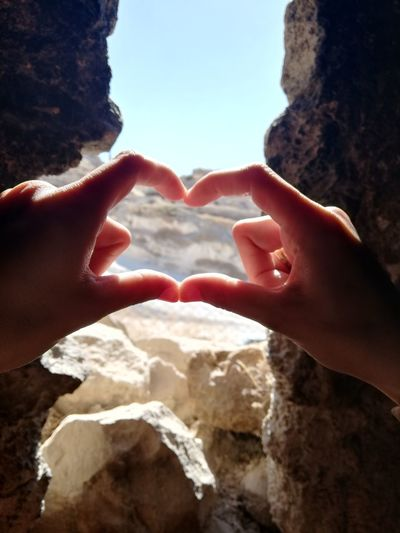 Close-up of hands making heart shape by rock