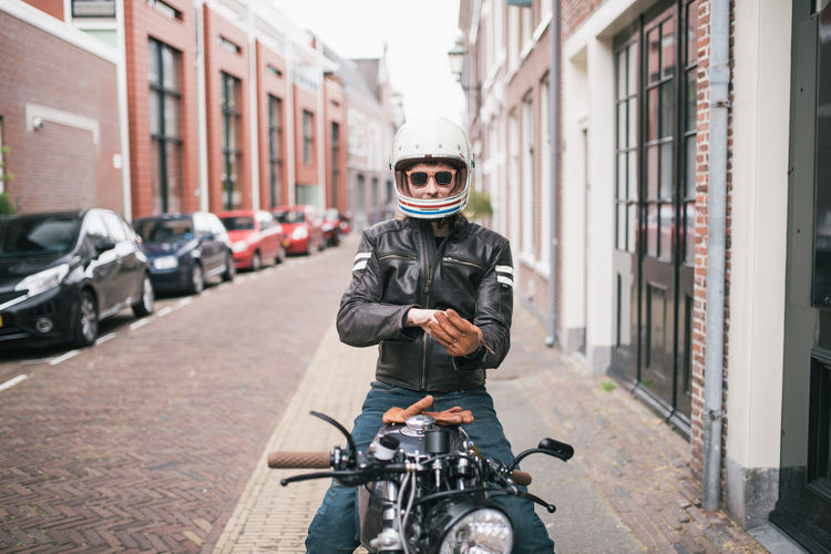Portrait of man siting on motorcycle at street in city