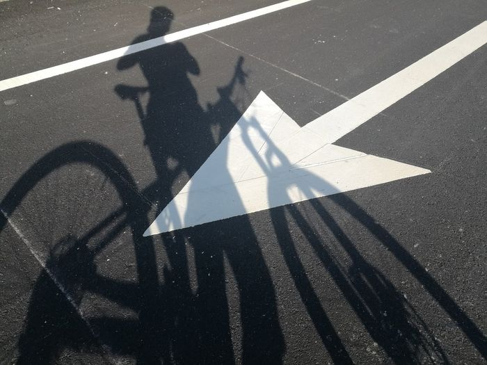 Shadow of woman with bicycle on road marking during sunny day