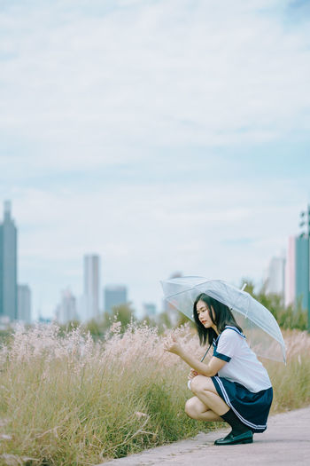 Side view of young woman with umbrella crouching by plants on field