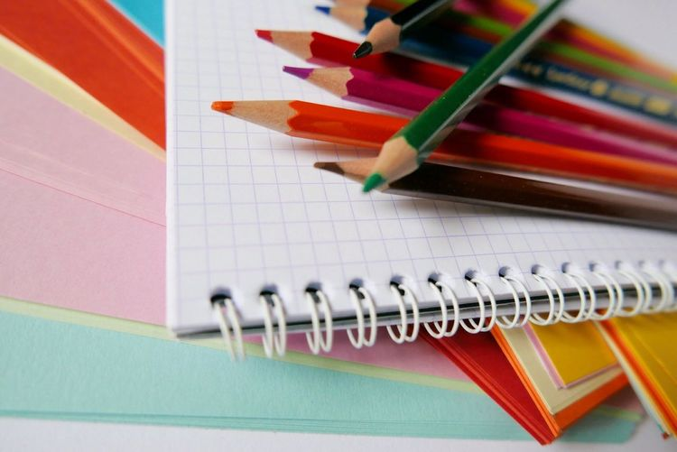 High angle view of colored pencils on spiral notebook