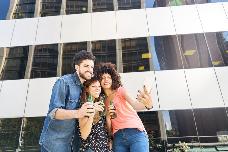 Woman taking selfie with friends while holding bottle over mobile phone
