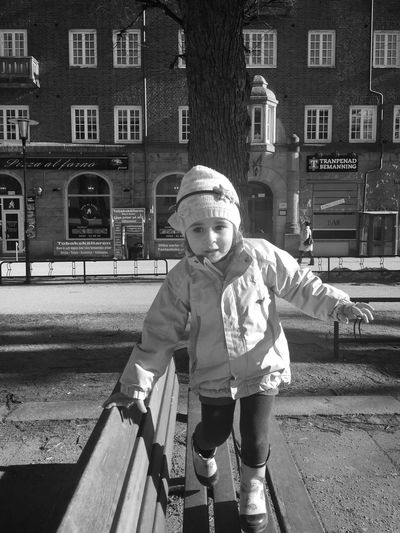 Sunny kid ... Shiny day Sunny Afternoon Lifestyle Downtown Girl Bench Seat Town Childhood Building Exterior One Person Architecture Built Structure Real People Playground Portrait Full Length Warm Clothing City Outdoors