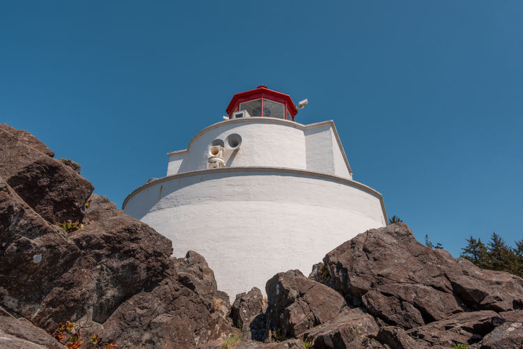 Low angle view of lighthouse by building against clear blue sky