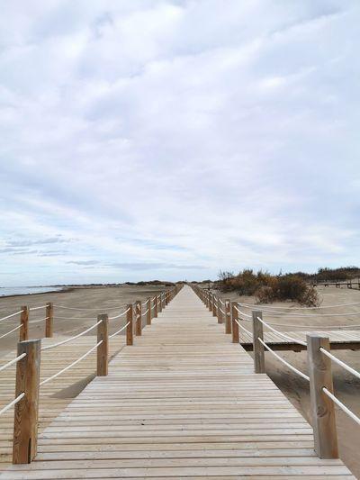 Wooden boardwalk on beach against sky