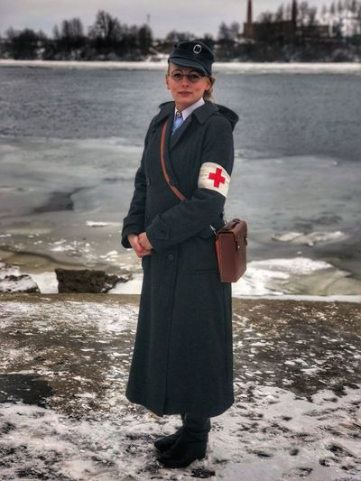 Portrait of army doctor standing against lake during winter