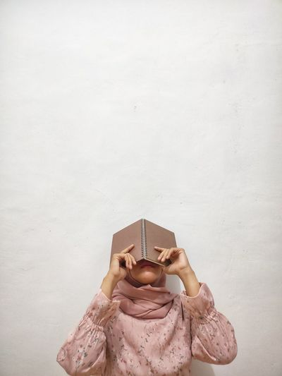 Midsection of woman holding book while standing against white wall
