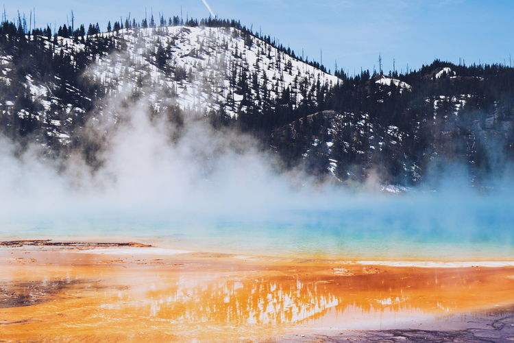Grand Prismatic Spring By Snow Covered Mountains At Yellowstone National Park