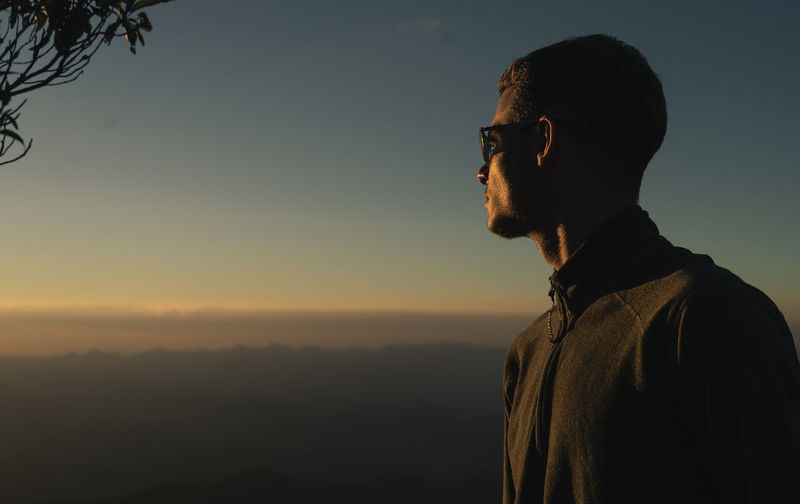Man looking at camera against sky during sunset