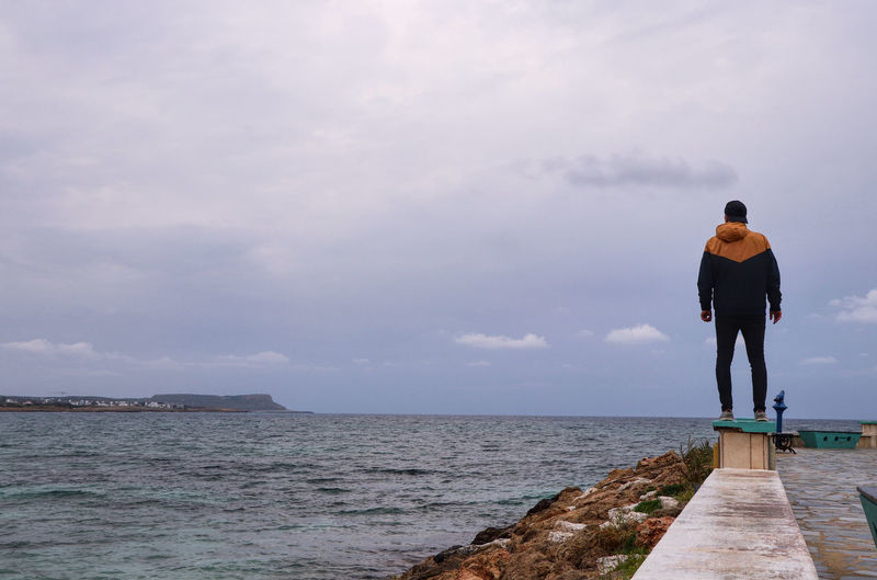 Rear view of man standing on pier over sea against sky